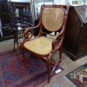An ornate bentwood armchair, with scroll arms and cane seat and back, in the manner of Thonet