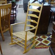 An Arts and Crafts Cotswold School style ladder-back rocking chair in ash, with rush seat,