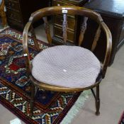 A stained beech bow-back desk chair with cane seat