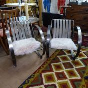 A pair of Art Deco design nickel plated steel armchairs, with circular sides and sheepskin seat pads