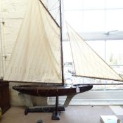A large 19th century wooden hulled model pond yacht, with masts and rigging, hull length 82cm, on