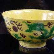 A Chinese yellow-ground Dragon bowl, depicting dragons chasing a flaming pearl, 6 character Kangxi