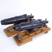 A pair of cast-iron barrelled model cannons on stained oak stands, overall barrel length 28cm,