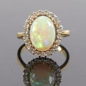 A large late 20th century 18ct gold cabochon opal and diamond cluster ring, set with oval cabochon