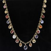 An Edwardian unmarked yellow metal gem set fringe necklace, set with graduated oval-cut gemstones,