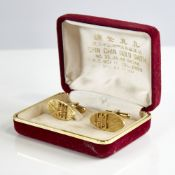 A pair of Bruneian 14ct gold cufflinks, oval panels with crosshatch decoration and applied character