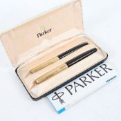 A Parker 51 black lacquered and gold plated fountain and ballpoint pen set, boxed
