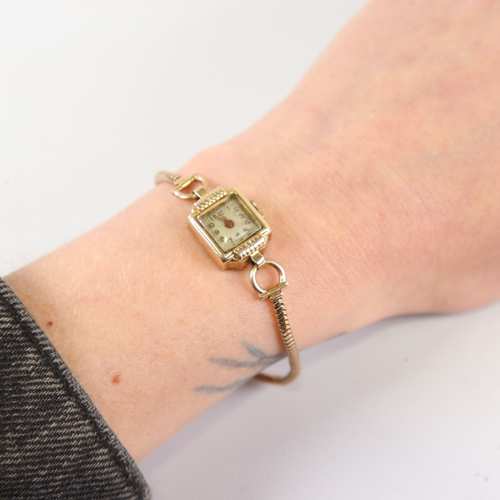 A lady's Vintage 14ct gold mechanical wristwatch, on 9ct snake link strap, not currently working, - Image 5 of 5