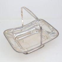 An Edwardian solid silver swing-handled fruit basket, rectangular pedestal form with gadrooned