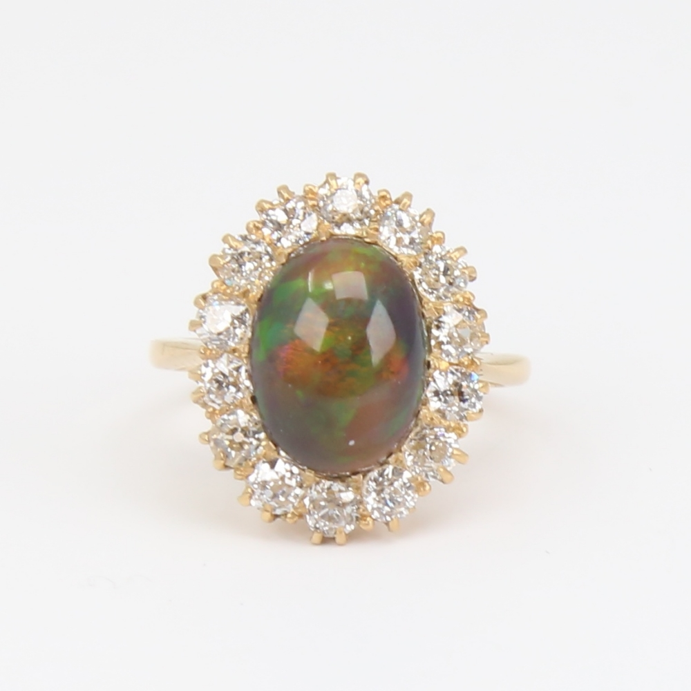 An early 20th century 18ct gold black opal and diamond cluster ring, set with oval high cabochon