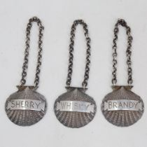 A set of 3 Elizabeth II cast-silver shell spirit decanter labels, comprising Whisky, Brandy and