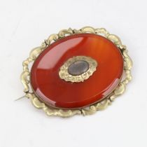A large Victorian oval mourning brooch, unmarked yellow metal settings with red banded agate and