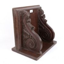 A large carved and stained oak wall bracket, with applied match striker, W36cm, D35cm, H25cm