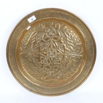 A large brass charger, relief embossed floral decoration, diameter 46cm