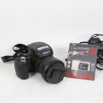 A Sony Cyber-Shot 10.3 megapixel CMOS DSC-R1 digital camera, with cables and booklets