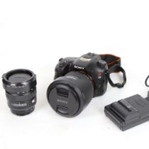 A Sony Alpha 57 digital camera, with lens accessories and softshell carrying bag