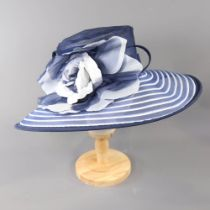 SUZANNE BETTLEY LONDON - Navy blue and white striped occasion hat, with flower and twirl detail,