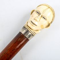 A malacca walking cane with African carved ivory head design handle, Continental silver collar,