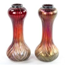 A pair of Loetz style iridescent red glass vases with moulded decoration, hallmarked silver rims,