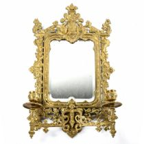 An ornate 19th century relief cast brass-framed wall mirror with candle sconces, overall height 51cm