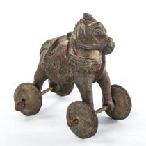 A Middle Eastern bronze toy roll-along horse on brass wheels, length 13cm Good condition
