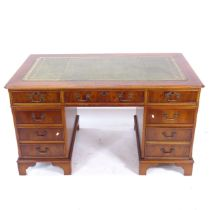 A reproduction yew wood twin-pedestal writing desk, with a tooled green leather skiver and fitted