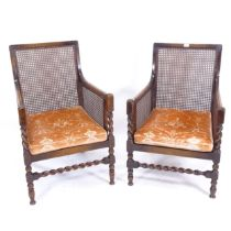 A pair of 1920s oak-framed bergere armchairs, with loose cushions (1 chair slightly shorter than the