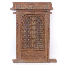 An ornate Indian hardwood and bras-mounted window, with allover relief carved decoration, W62cm,