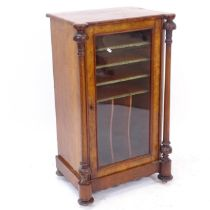 A Victorian walnut and satinwood-strung music cabinet, with single glazed door and carved and fluted