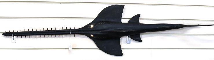 A Vintage black painted hardwood fishmonger's sawfish advertising sculpture, length 140cm
