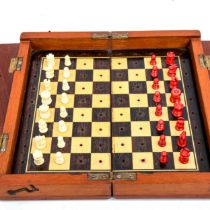 A 19th century mahogany travelling chess set, with carved red and white stained ivory chess