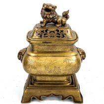 A Chinese polished bronze incense burner and cover on stand, with Dog of Fo knop and engraved