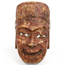 A Chinese Nuo opera mask of Tudi Gong, relief carved and painted wood, on wooden stand, height