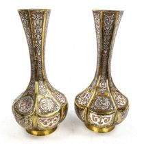 A pair of Persian brass narrow-necked vases, with intricate inlaid silver and