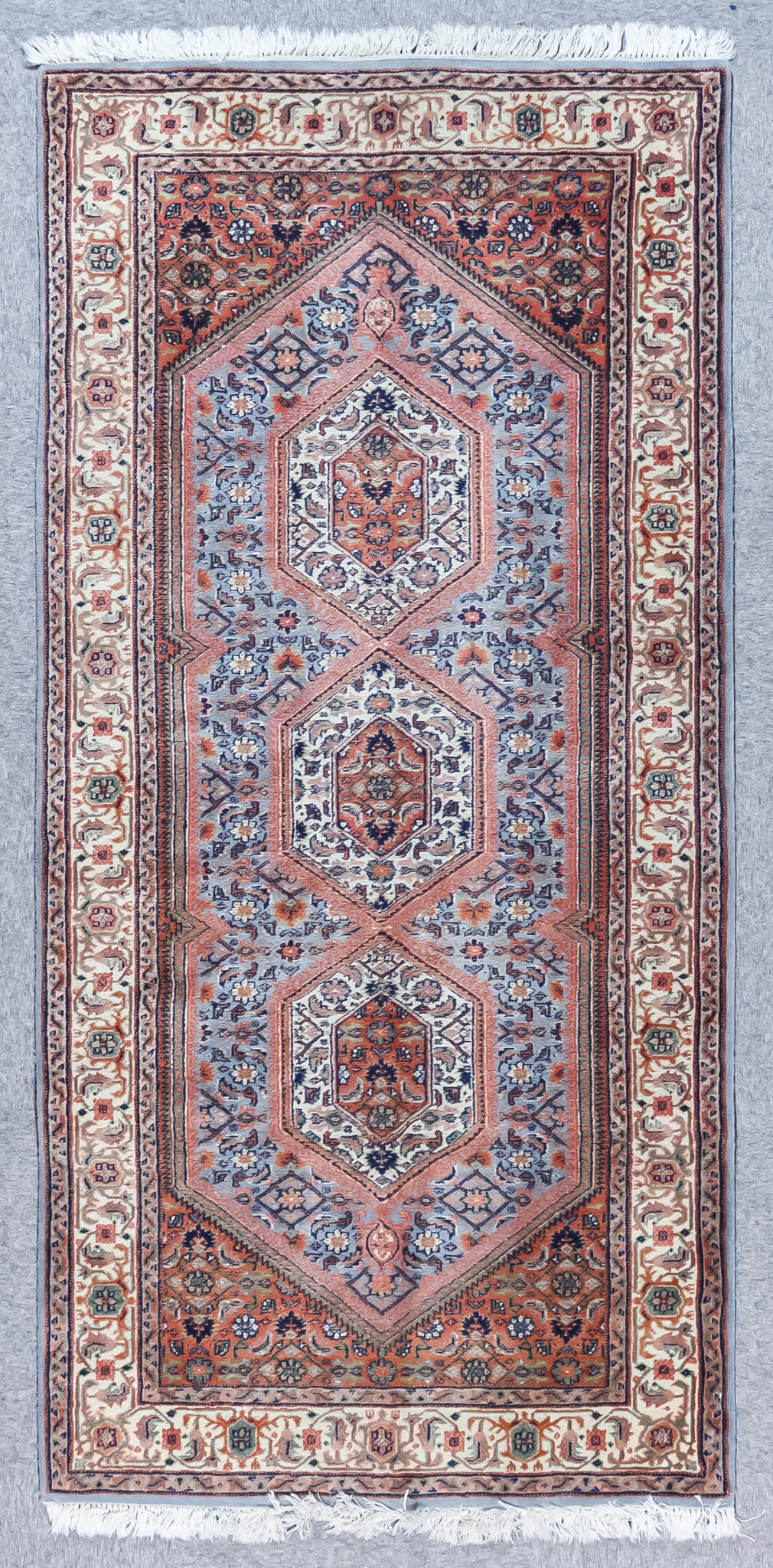 A Tabriz Runner, Mid 20th Century, woven in fawn, ivory and blue with three hexagonal floral