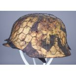 A German World War II Helmet, painted in camouflage pattern, with chicken wire attached to