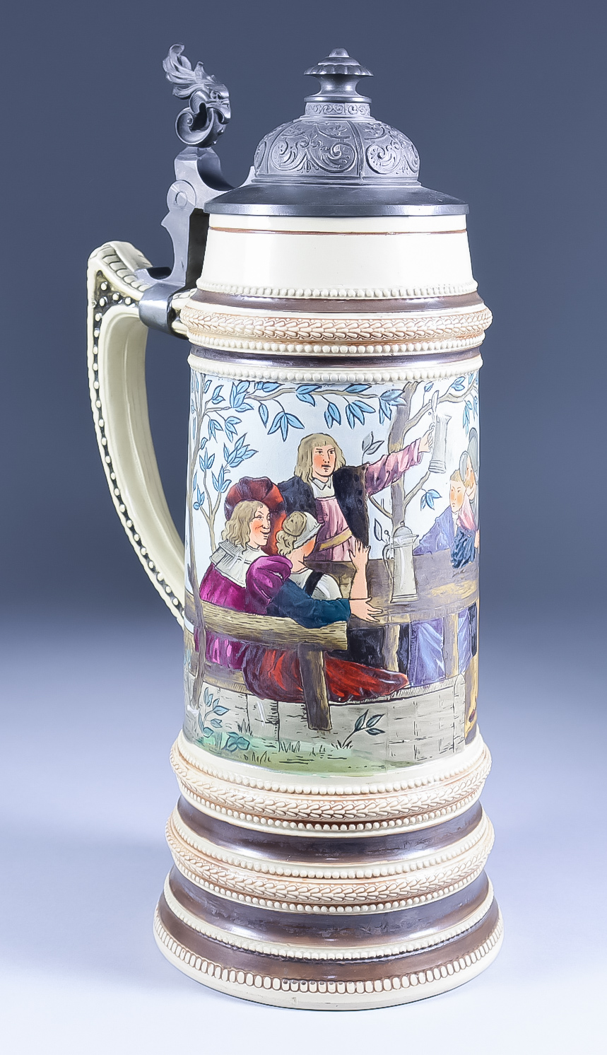 A German Stoneware and Pewter Mounted Stein in Mettlach Style, decorated with figures drinking
