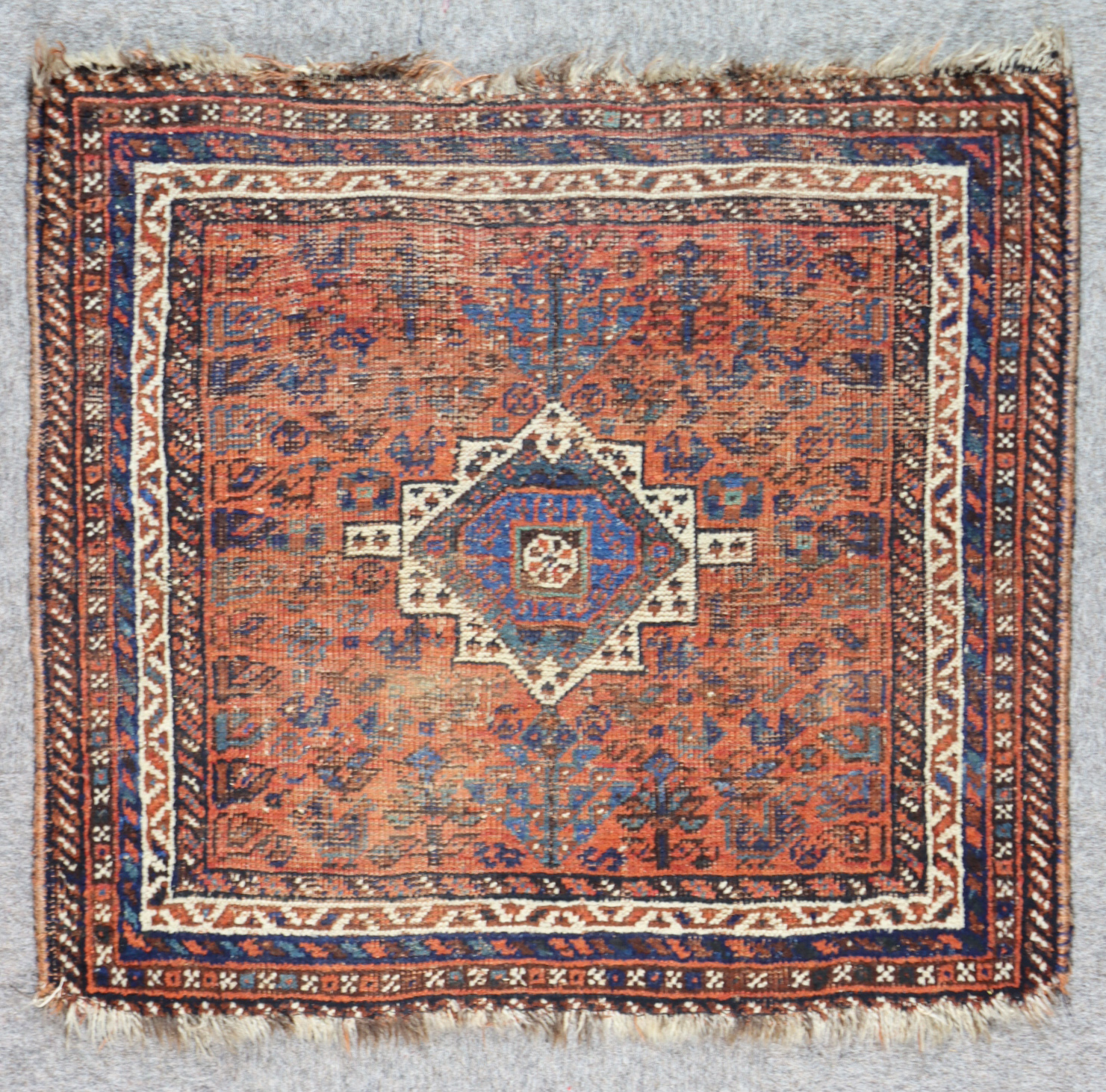 A Late 19th/Early 20th Century Persian Juval woven in colours of navy blue, ivory and terracotta,