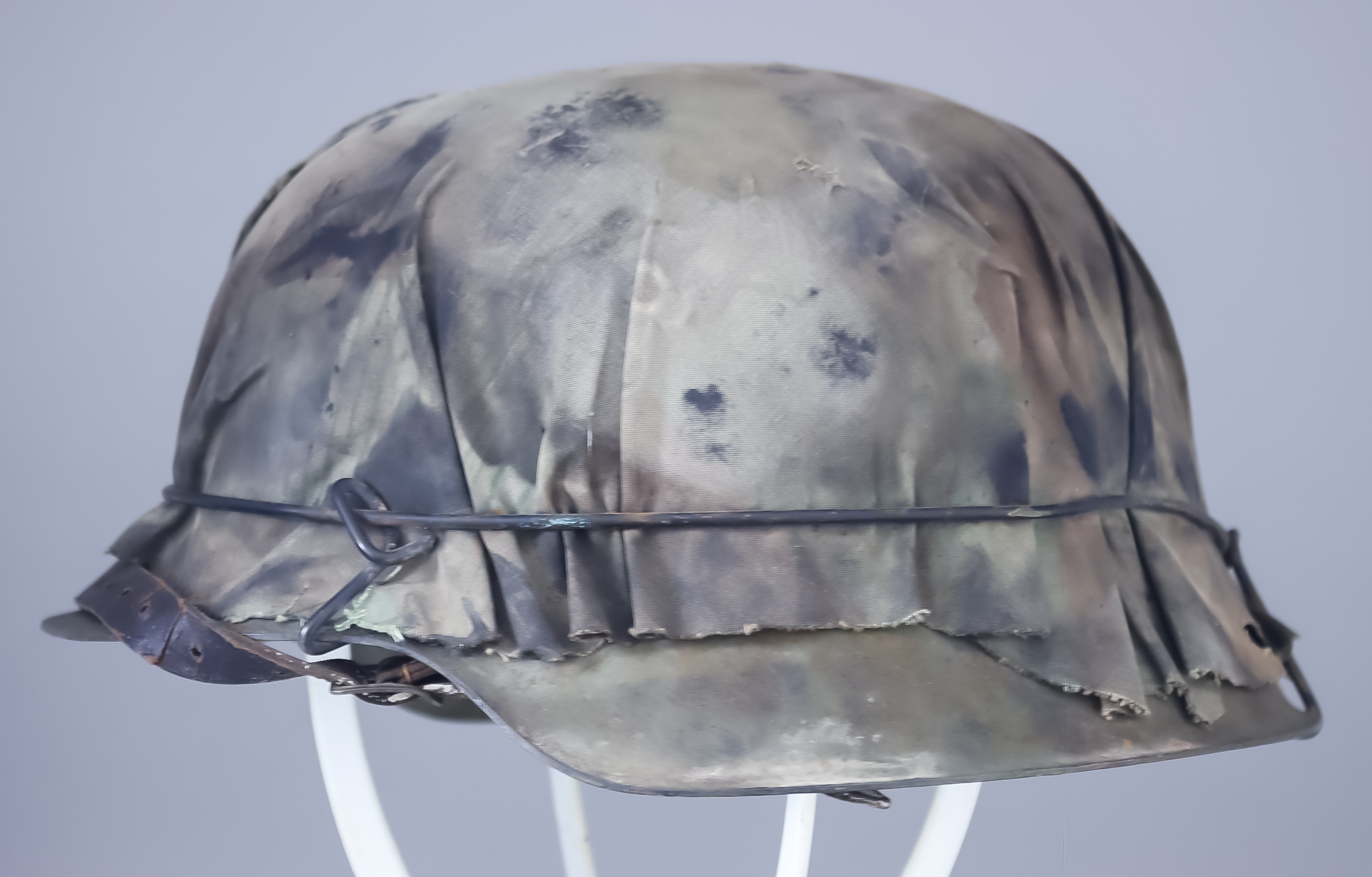 A German World War II German Helmet, covered in camouflage material with wire binding