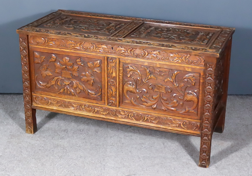 A Panelled Oak Coffer, the whole boldly carved with dragons, fruiting vines and leaf scroll