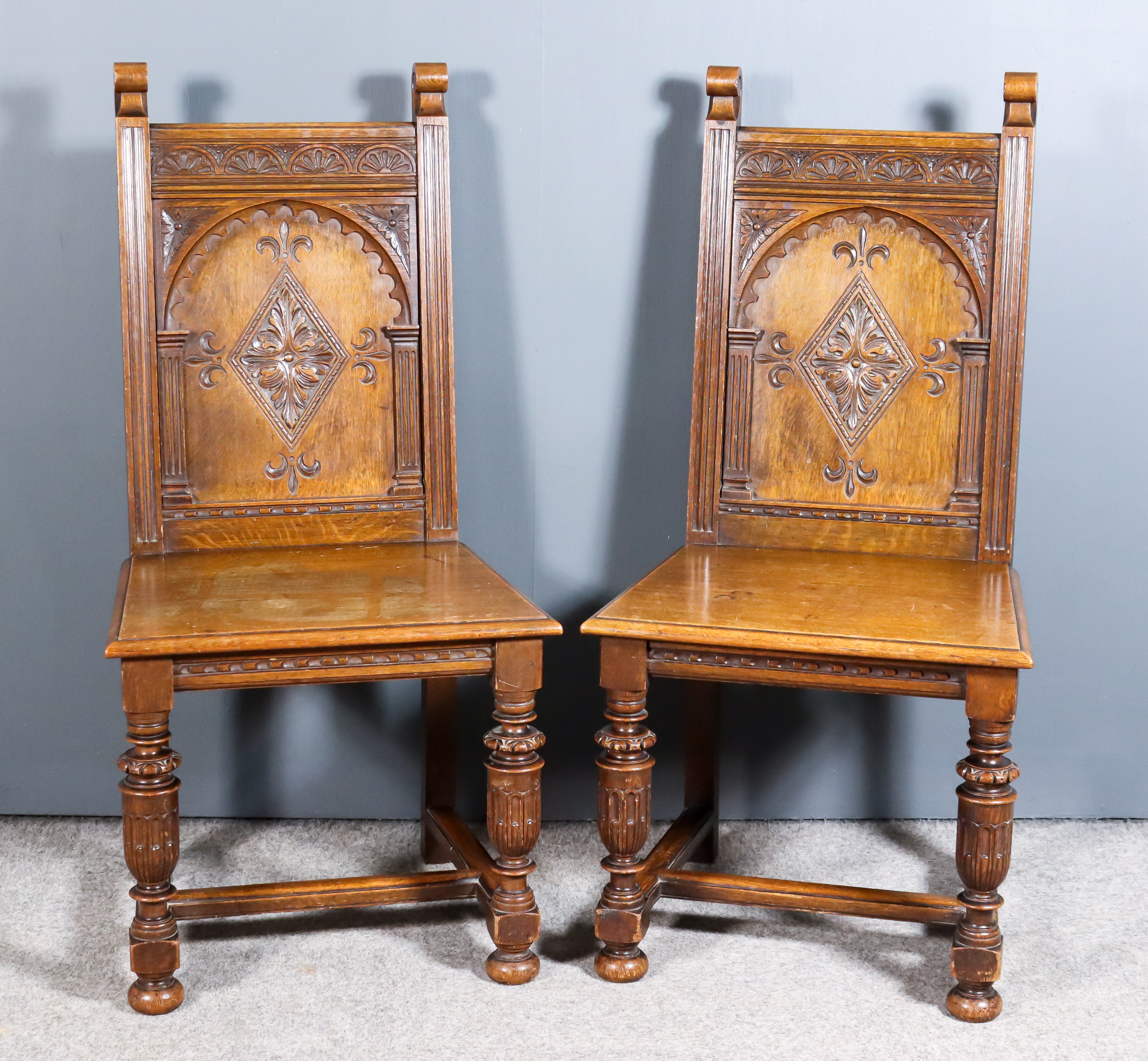 """A Pair of Oak Hall Chairs of """"17th Century"""" design, the back with scroll terminals, the panels"""