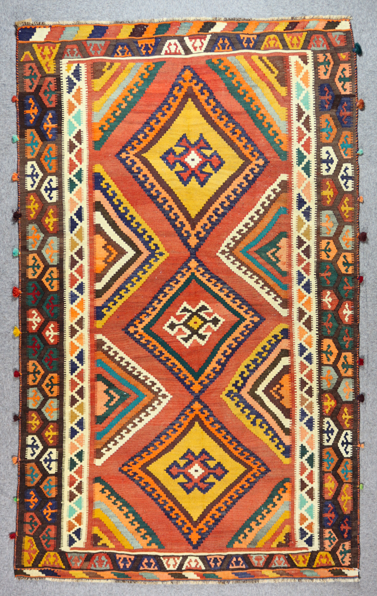 A Qashqai Kilim, Early 20th Century, woven in colours, with three lozenge shaped medallions filled