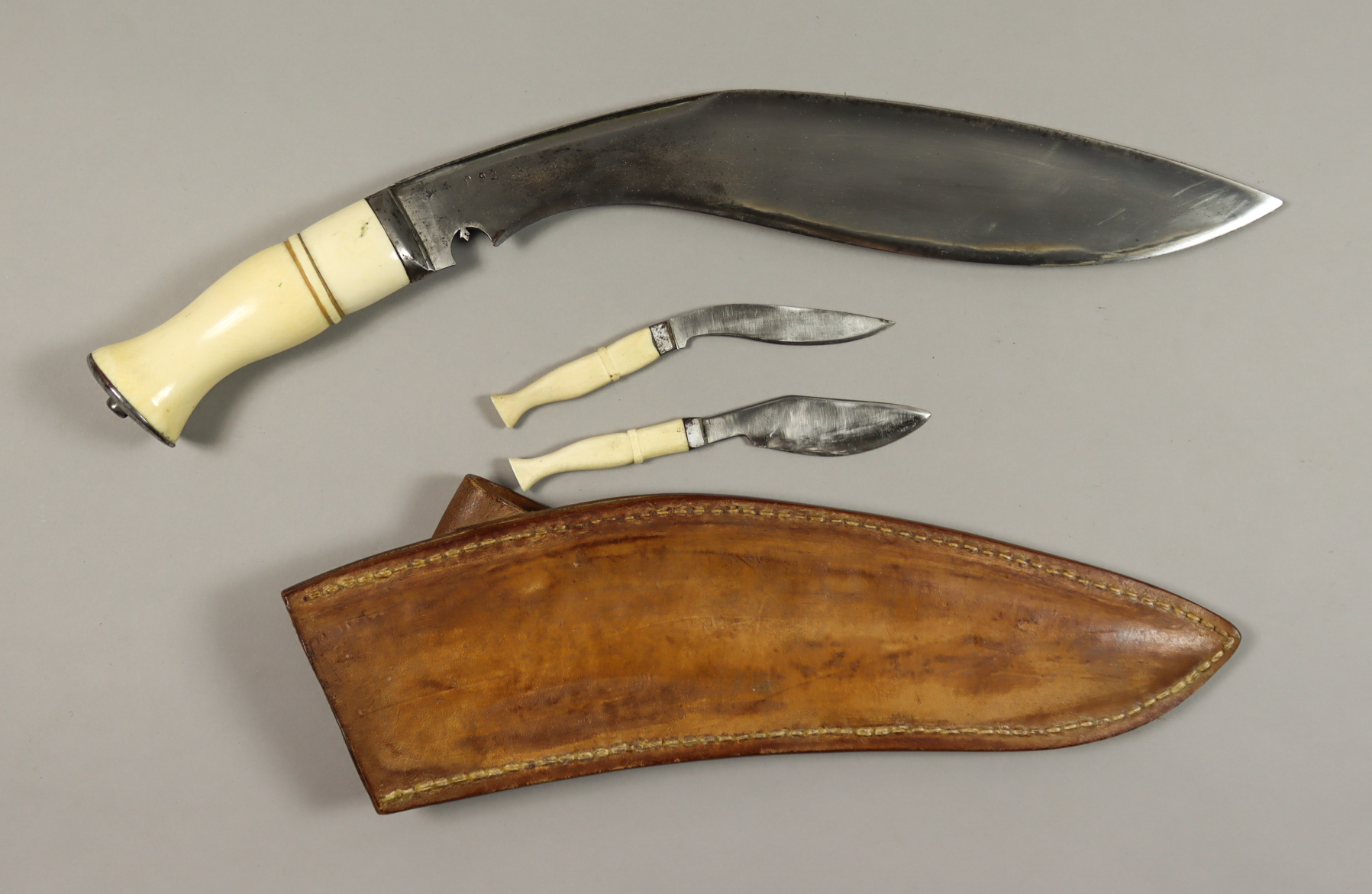 A Good 20th Century Broad Leaf Kukri, No. 899, in substantial leather scabbard, fitted with bone