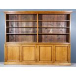 A Victorian Oak Bookcase, the upper part with moulded cornice, fitted six open shelves, the base
