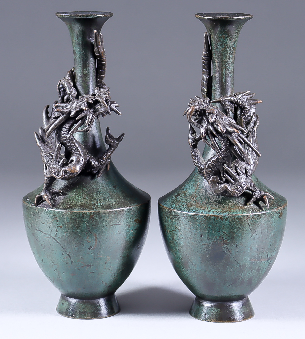 A Pair of Japanese Green and Brown Patinated Bronze Vases, Meiji Period, each cast with a dragon