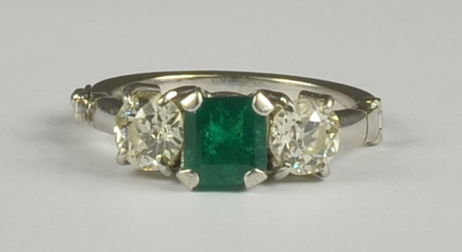 An Emerald and Diamond Three Stone Ring, Modern, 18ct white gold, set with a centre emerald,