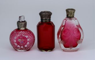 An Edward VII Silver Topped Cranberry Glass Scent Bottle and Two Other Scent Bottles, the