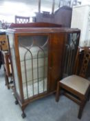 A MAHOGANY DISPLAY CABINET WITH LEDGE BACK, SERPENTINE FRONT, CENTRE PANEL FLANKED BY ASTRAGAL