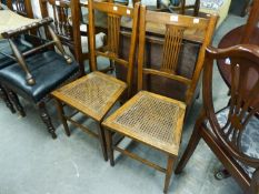 A PAIR OF OAK BEDROOM CHAIRS WITH PIERCED SPLAT BACK AND CANE SEATS (2)