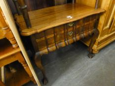 A CONTINENTAL DARKWOOD TWO DRAWER CUTLERY CHEST/SIDE TABLE WITH SHAPED TOP AND RAISED ON LONG